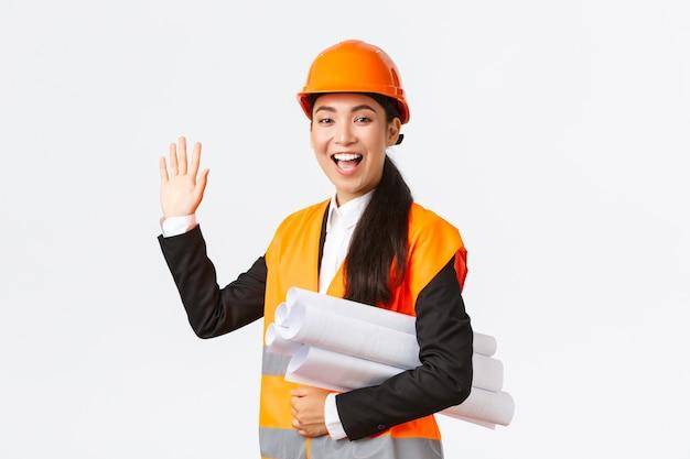 フレンドリーで陽気なアジアの女性建設マネージャー、安全ヘルメットとジャケットの主任建築家、青写真、建築プロジェクトの文書を運ぶ、挨拶するために手を振る、誰かに挨拶する