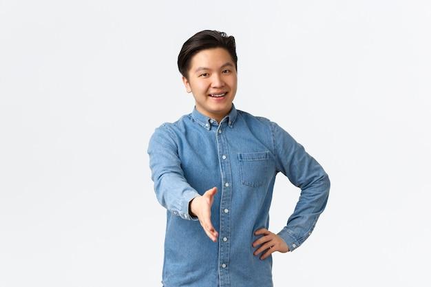 Amichevole uomo asiatico allegro in cerca di lavoro, vieni a intervistare, tendendo la mano per stretta di mano, salutando qualcuno, benvenuto in ufficio, salutando con un sorriso felice, sfondo bianco