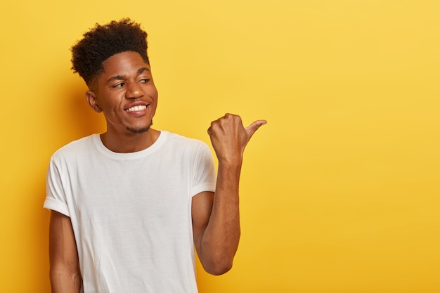 Friendly cheerful dark skinned hipster man discusses interesting copy space and points thumb away on right side, shows some place or direction, has curly trendy haircut, wears casual white t shirt