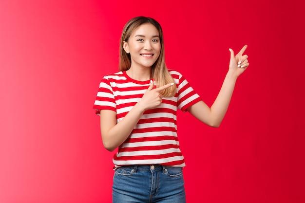 左上隅を指しているフレンドリーで陽気なハンサムな若いブロンドの韓国の女の子は、完璧な場所を提案し、広く笑顔の製品をお勧めし、良いコピースペースを紹介し、赤い背景を立てます。