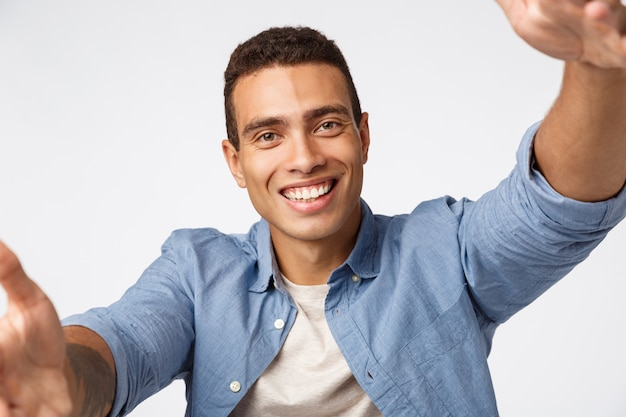 Friendly cheerful masculine guy in casual outfit, holding camera both hands