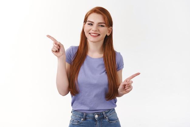Amichevole, allegra ed estroversa donna carina sorridente con lunghi capelli rossi, che punta di lato, mostra striscioni sinistro e destro, invita i link al check-out, promuovono prodotti, due varianti, muro bianco