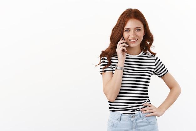 Friendly cheerful redhead caucasian girl in striped t-shirt, hold hand on waist, calling boyfriend, smiling joyfully, hold smartphone near ear, talking, making food order, standing white wall