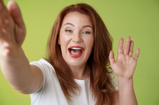 Amichevole donna di mezza età rossa allegra estendere il braccio tenere la fotocamera prendendo selfie agitando la palma ciao ciao saluto sorridente ampiamente benvenuta figlia parlando videochiamata mobile internet muro verde