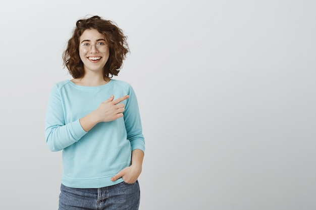 Friendly cheerful woman pointing finger right and smiling as showing copyspace