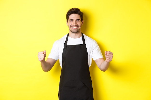 Friendly coffee shop waiter standing with raised hands, place for your sign or logo, standing over yellow background.