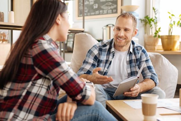 フレンドリーな同僚。ノートを持って、女性の同僚と何かを話している間笑顔で陽気なハンサムなひげを生やした男