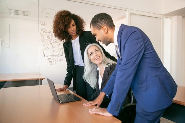 フレンドリーな同僚が事務室でプロジェクトについて議論し、笑みを浮かべています。テーブルに座ってパートナーと話している白髪のコンテンツビジネスウーマン。チームワーク、ビジネス、管理の概念