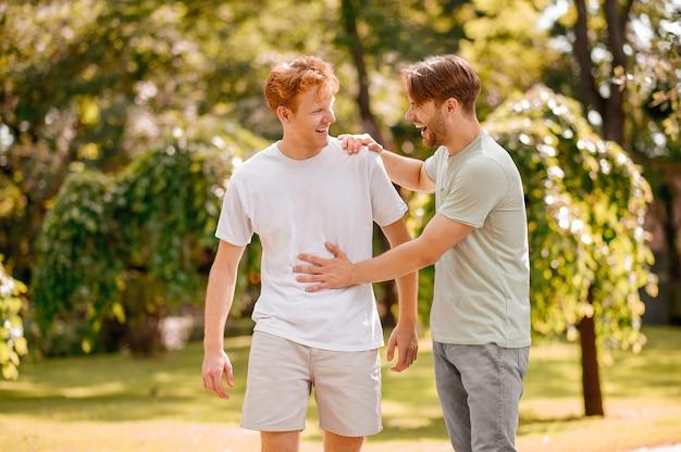 친절한 의사 소통. 밝은 티셔츠를 입은 친절한 빨간 머리와 검은 머리 남자들은 화창한 날 녹색 공원에서 웃고 의사 소통합니다.