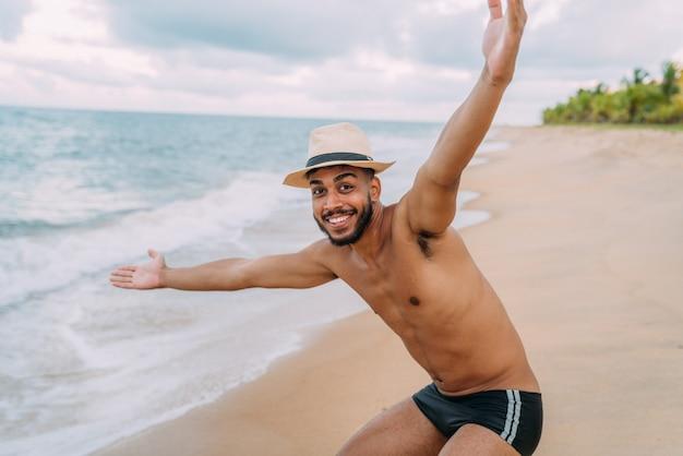 ビーチでカメラを見て両手を広げてフレンドリーな自信と笑顔の若いラテンアメリカ人