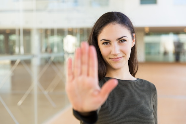 Friendly confident beautiful woman making hand stop gesture