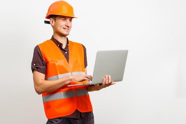 あなたのメッセージのための黒いスペースでラップトップを持っているフレンドリーな建設労働者。白で隔離。