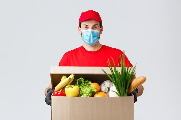 Дружелюбный курьер в маске и перчатках доставляет коробку с едой клиенту во время коронавируса, доставляет бесконтактно