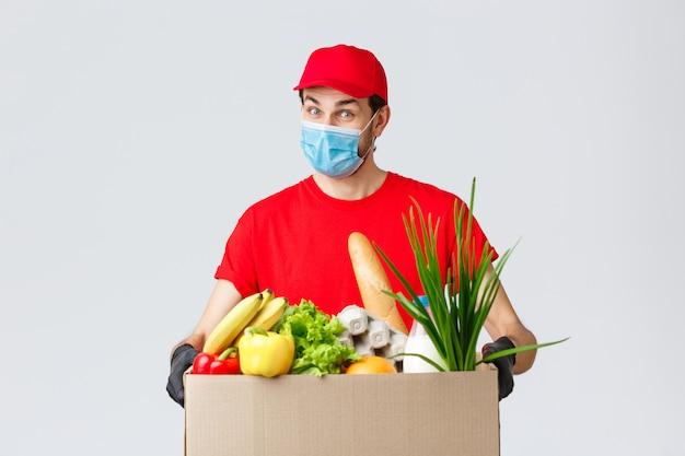 Дружелюбный курьер в лицевой маске и перчатках, в красной форме доставляет коробку с едой заказчику онлайн, бесконтактно доставляет