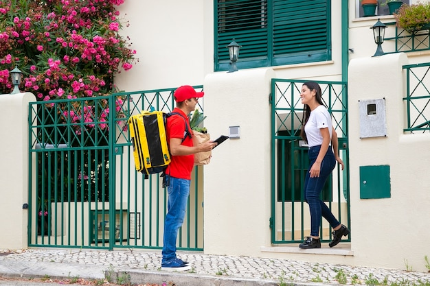 등온 배낭이있는 친절한 택배가 고객 문에 음식을 배달합니다. 태블릿, 식료품가 게에서 종이 패키지와 여자 회의 배달 남자. 배송 또는 배달 서비스 개념