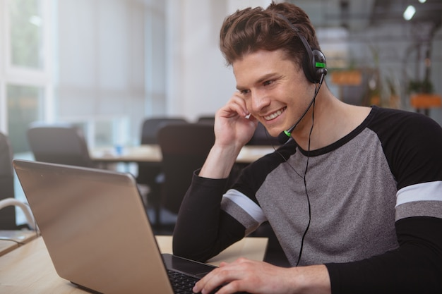 Friendly customer support operator with headset working at call center
