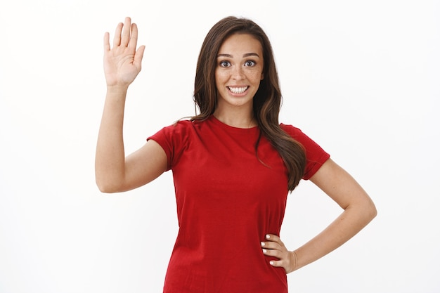 Friendly cute brunette girl in red t-shirt raising hand up, waving palm saying hello, greeting nicely newcomers, invite guests with warm welcome, standing white wall, say bye