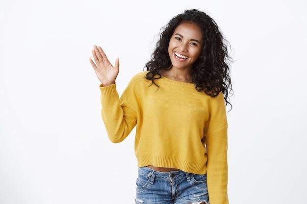 노란 스웨터를 입은 친근한 곱슬머리 소녀가 손바닥을 들고 손을 흔들며 인사하고, 머리를 갸웃거리며 인사하고, 작별 제스처를 하고, 흰 벽에 서 있습니다.