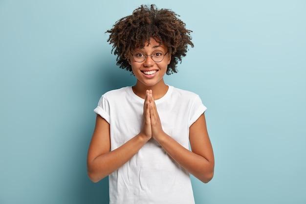 Amichevole femmina dalla pelle scura tiene i palmi insieme sul petto, mostra il gesto del namaste, chiede aiuto, ha un'espressione felice, indossa una maglietta bianca, occhiali ottici, isolato su un muro blu.