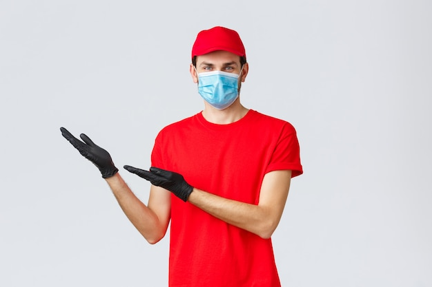 Friendly delivery man in uniform, medical face mask and gloves introduce new promo