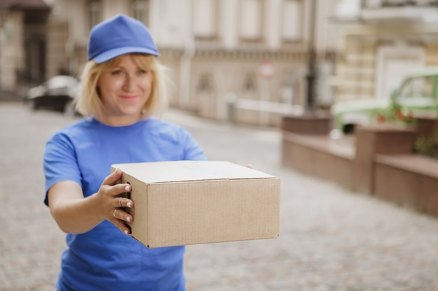 Friendly delivery woman in blue uniform on the city street