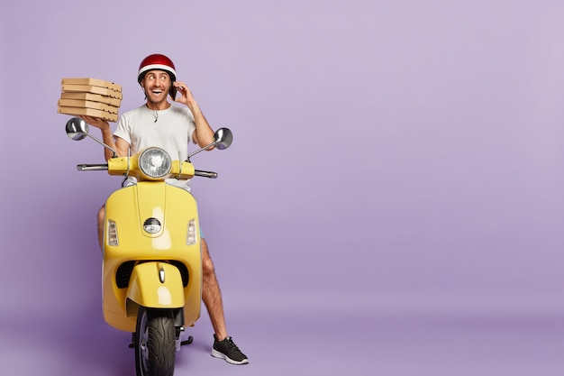 Friendly deliveryman driving scooter while holding pizza boxes