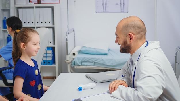机に座っている子供とハイタッチをしているフレンドリーな医者。病院のキャビネットで医療サービスのx線治療検査を提供する医療の専門医