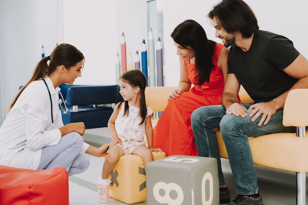 Friendly doctor and family at pediatrician office