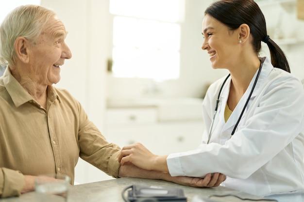 彼女の年配の患者と仲良くしているフレンドリーな医者