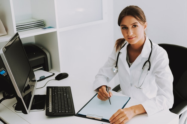 Friendly doctor practitioner is writing in office