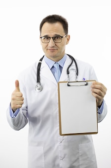 Friendly doctor with blank clipboard showing like sign with thumb up with copy space