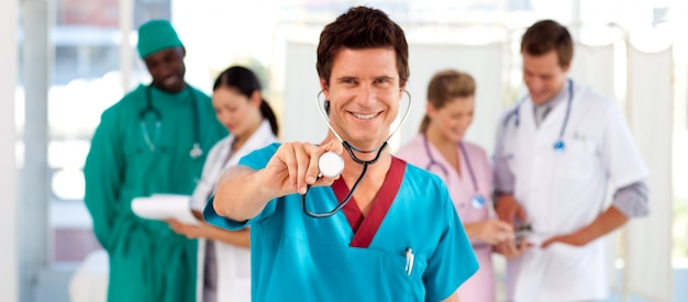 Friendly doctor with his team in the background