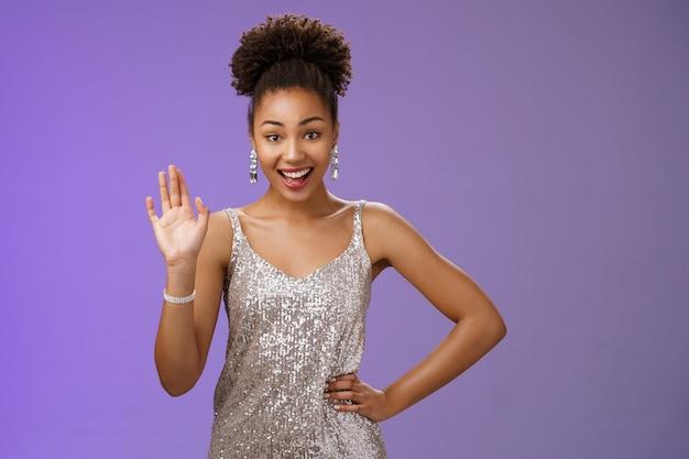 Friendly elegant african-american young 20s woman wearing elegant silver glittering dress hold hand waist waving hello greeting gesture say hi informally meet friend talking blue background.