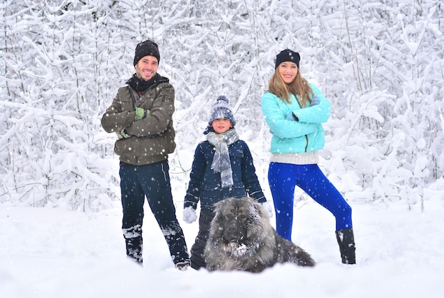 Friendly family: mother, father, son and dog outdoors. winter forest.