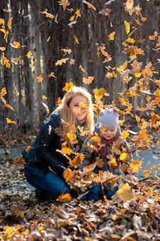 公園の葉の落下中に散歩でフレンドリーな家族