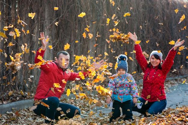 공원에서 낙엽이 떨어지는 동안 산책을 하는 친절한 가족