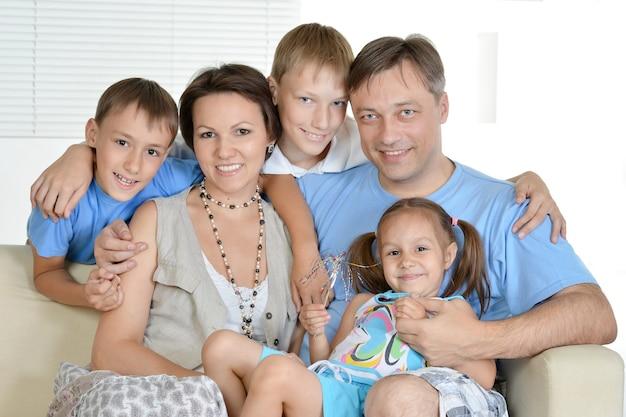 一緒にソファで家で休んでいるフレンドリーな家族