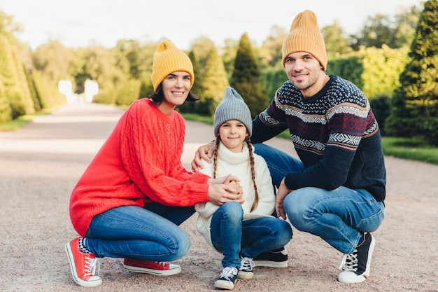 Friendly family wear knitted clothes, have walk together, admire splendid autumn weather