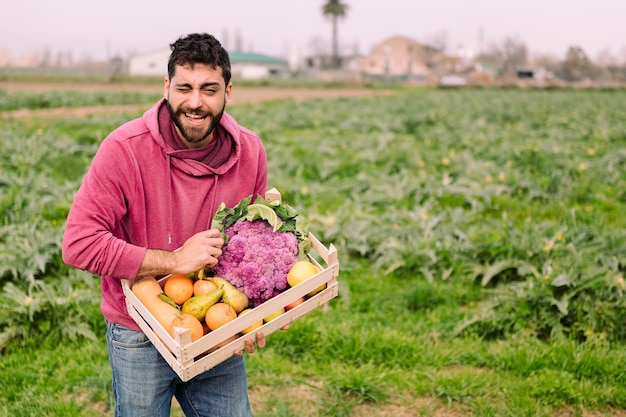 야채와 함께 나무 상자와 친절 한 농부