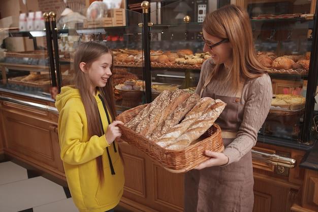 Friendly female baker helping young girl choosing fresh bread to buy