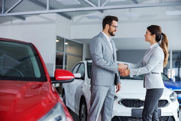 Дружелюбный женский продавец автомобилей, пожимая руку клиенту, стоя в салоне автомобиля.
