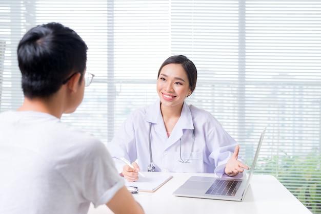 책상에 앉아 환자의 손을 잡고 친절한 여성 의사의 손