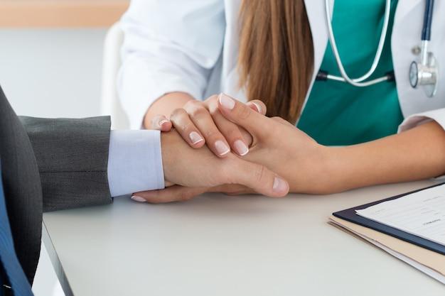 Дружелюбная женщина-врач держит пациента за руку, чтобы поддержать его