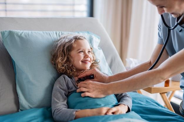 聴診器を持つフレンドリーな女性医師は、病院、中央部のベッドで小さな女の子を調べます。