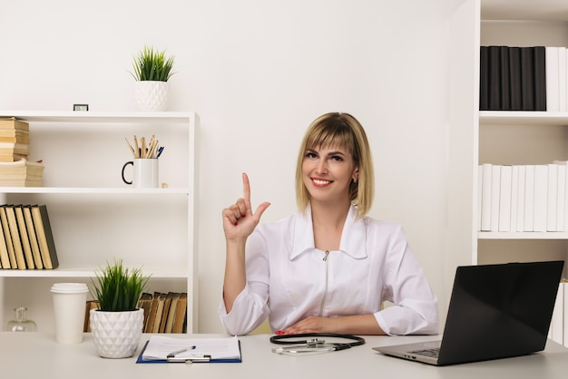 Friendly female doctor works at her desk in the office pointing up
