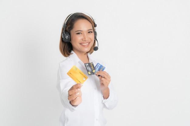 フレンドリーな女性のヘルプライン オペレーターまたはコール センターが空白のクレジット カードを示し、白い表面に腕を組んでいるヘッドセット