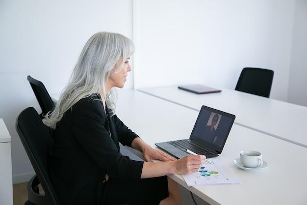 コーヒーを飲みながらテーブルに座って図を分析しながら、ラップトップでビデオチャットを介して同僚と話しているフレンドリーな女性サラリーマン。オンラインコミュニケーションの概念