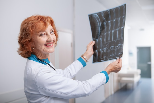 Friendly female oncologist smiling to the camera, holding mri scan of a patient