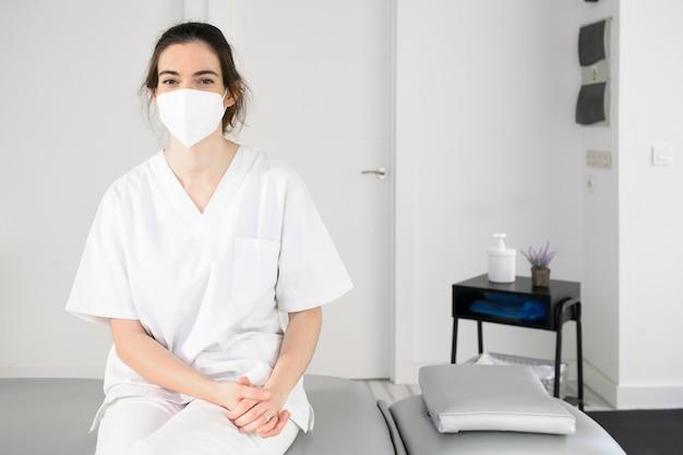 코로나 바이러스 전염병 동안 보호 얼굴 마스크를 착용하는 현대 병원에서 포즈를 취하는 친절한 여성 물리 치료사