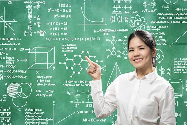 Friendly female teacher write on blackboard